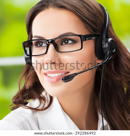 Portrait of happy smiling cheerful young brunette businesswomen, support phone female operator or call center worker, in headset and glasses. Help and consulting concept.  - stock photo