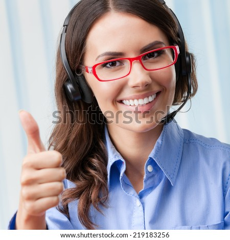 Portrait of happy smiling cheerful young support phone operator in headset, showing thumbs up gesture, at office