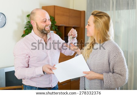 Portrait of happy smiling couple with contract for buying apartment and keys. Focus on woman - stock photo