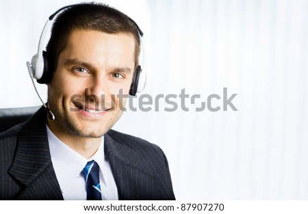 Portrait of happy smiling customer support phone operator in headset at office. You can use right part for slogan, text or banner. - stock photo