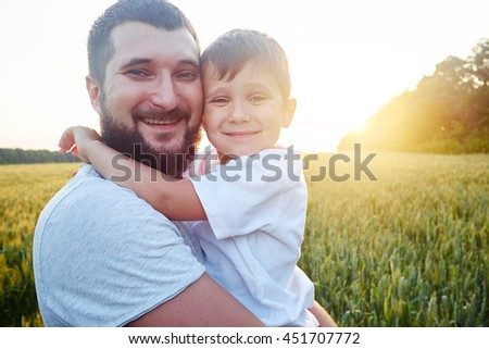Portrait of happy smiling dad and son in the sunlit field during sunset