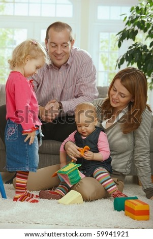 Portrait of happy smiling family of dad, mum and two baby girls at home.? - stock photo