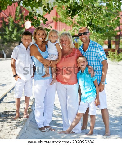 Portrait of happy smiling family with three children sitting together in full length. - stock photo