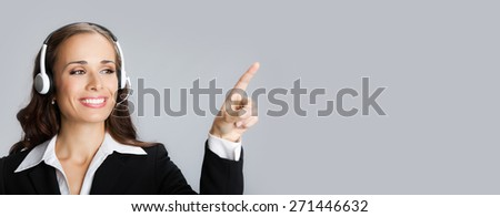 Portrait of happy smiling female customer support phone operator in headset pointing at something or blank copyspace area for text or slogan - stock photo