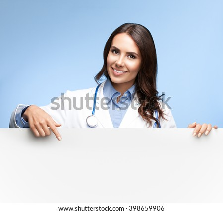 Portrait of happy smiling female doctor showing blank signboard with copyspace for slogan or text, on bright blue background - stock photo