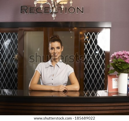 Portrait of happy smiling female receptionist at hotel. - stock photo