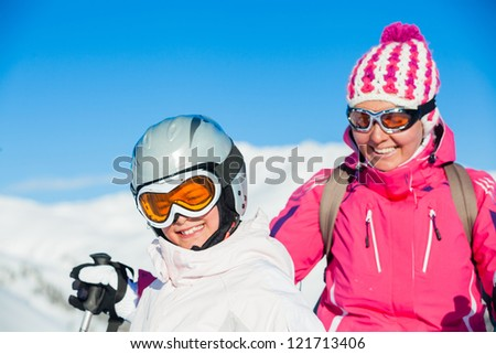 Portrait of happy smiling girl in ski goggles and with her mother, Zellertal, Austria. Focus on the girl - stock photo