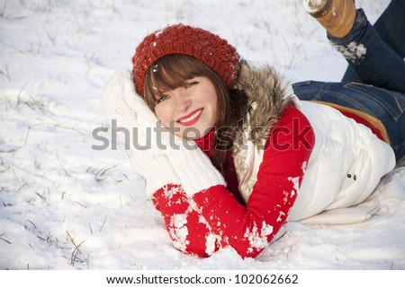 Portrait of happy smiling girl laying down on the snow in winter