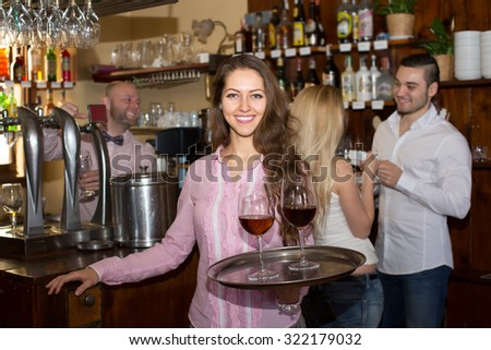 Portrait of happy smiling girl working in modern bar as waitress - stock photo