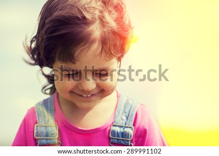 Portrait of happy smiling little girl walking on sunny windy day  - stock photo