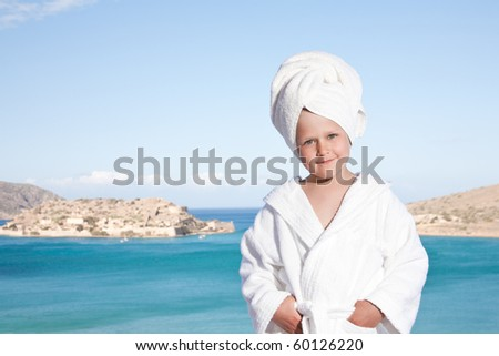 Portrait of happy smiling little girl with towel on the head in white bathrobe relaxing on terrace and looking at camera on the sea background - stock photo