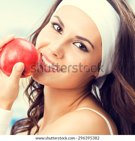 Portrait of happy smiling lovely woman with red apple, at fitness center or gym - stock photo