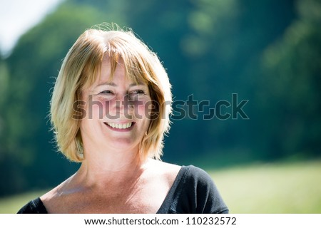 Portrait of happy smiling mature woman - outdoor in nature - stock photo