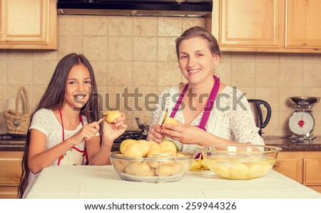 Portrait of happy, smiling mother and daughter cooking dinner, preparing food isolated background home kitchen. Positive family emotions, face expression, life perception. Healthy eating concept - stock photo