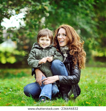 Portrait of happy smiling mother and son in a park - stock photo