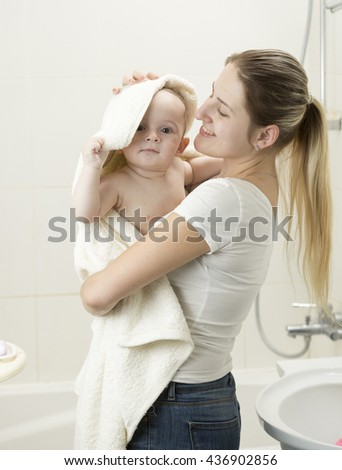 Portrait of happy smiling mother wiping her baby with towel after having bath - stock photo