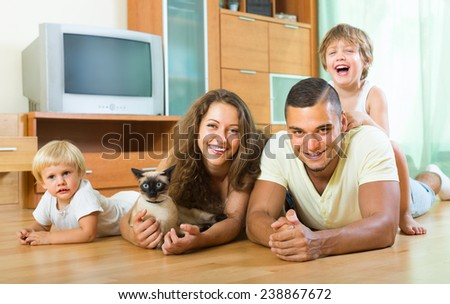 Portrait of happy smiling parents and two daughters with Siamese at home - stock photo