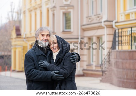Portrait of happy smiling retired couple wearing coats outdoors - stock photo
