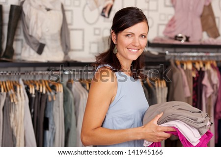 Portrait of happy smiling woman holding stack of clothes in boutique