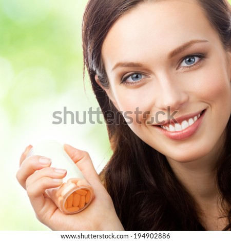 Portrait of happy smiling woman showing bottle with pills, outdoors