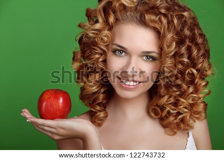 Portrait of happy smiling woman with long glossy hair holding red apple - stock photo