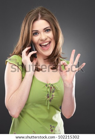 Portrait of happy smiling woman with phone dressed in a green blouse, Isolated on gray background