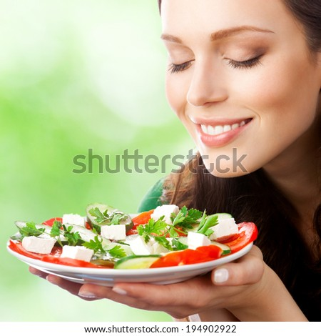 Portrait of happy smiling woman with plate of salad, outdoors - stock photo