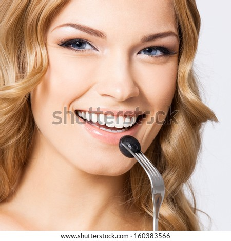 Portrait of happy smiling young beautiful woman eating black olive, over gray background - stock photo
