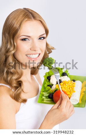 Portrait of happy smiling young beautiful woman with healthy vegetarian salad with broccoli, over gray background