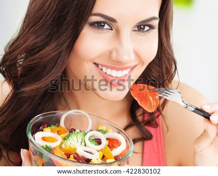 Portrait of happy smiling young brunette woman with vegetarian vegetable salad - stock photo