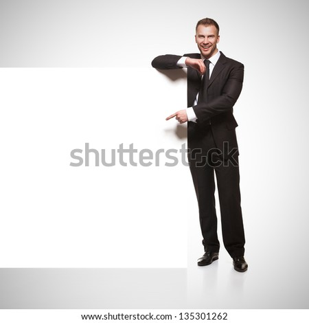 Portrait of happy smiling young business man showing blank signboard isolated on grey gradient background - stock photo