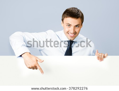 Portrait of happy smiling young business man showing blank signboard, over grey background - stock photo