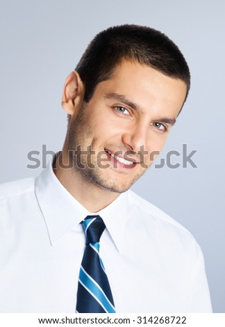 Portrait of happy smiling young businessman, posing at studio, against grey background - stock photo