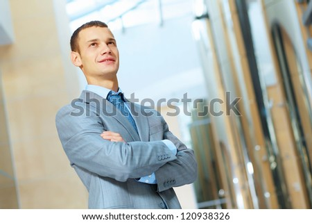 Portrait of happy smiling young businessman, standing in office - stock photo