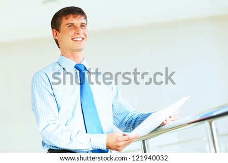 Portrait of happy smiling young businessman, standing in office