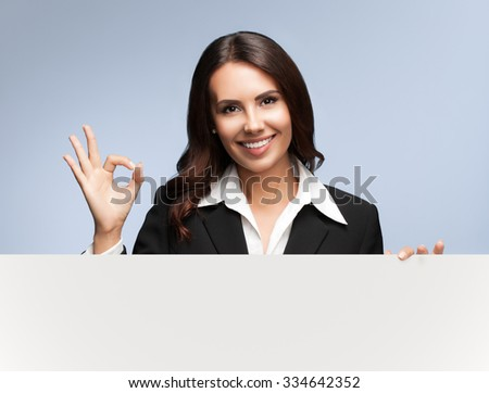 Portrait of happy smiling young businesswoman in black suit, showing blank signboard with blank copyspace area for slogan or text, over grey background, showing okay gesture - stock photo
