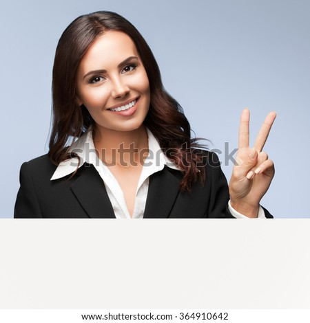 Portrait of happy smiling young businesswoman in black suit, showing blank signboard with blank copyspace area for slogan or text, over grey background, showing two fingers or victiory gesture - stock photo
