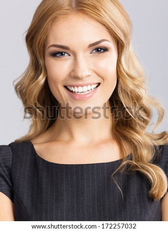 Portrait of happy smiling young cheerful business woman, on gray background - stock photo