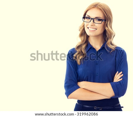 Portrait of happy smiling young cheerful businesswoman in blue clothing and glasses in crossed arms pose - stock photo