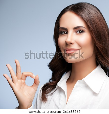 Portrait of happy smiling young cheerful businesswoman, showing okay hand sign gesture, over grey background - stock photo