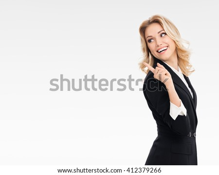 Portrait of happy smiling young cheerful businesswoman, showing something or blank copyspace area for slogan or text message, on grey background, with blank copyspace area for text or slogan