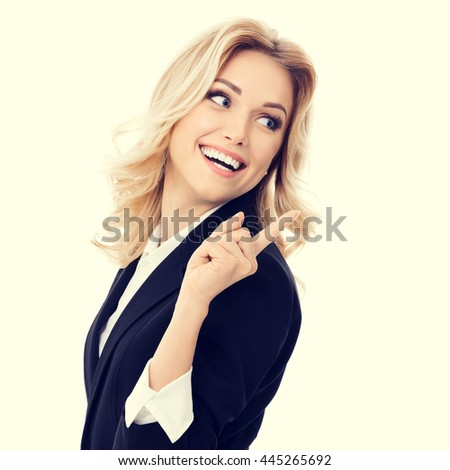 Portrait of happy smiling young cheerful businesswoman, showing something or blank copyspace area for slogan or text message - stock photo
