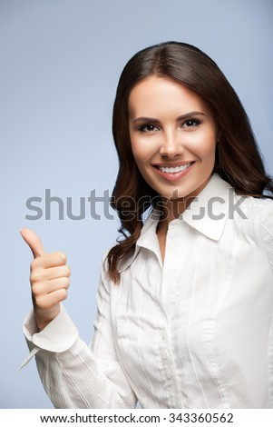 Portrait of happy smiling young cheerful businesswoman, showing thumb up hand sign gesture - stock photo