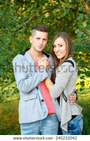portrait of happy smiling young couple in love embracing outdoor at sunny day - stock photo