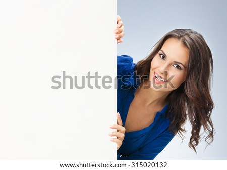 Portrait of happy smiling young woman in blue clothing, showing blank signboard with blank copyspace area for slogan or text, posing at studio - stock photo