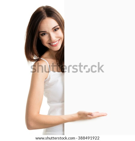 Portrait of happy smiling young woman in white tank top casual smart clothing, showing empty blank signboard with copyspace area for text or slogan, isolated against white background