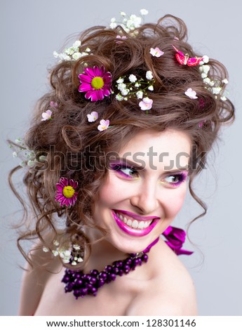 Portrait of happy smiling young woman with flowers in her hair and bright makeup isolated on white