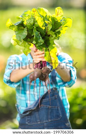 Portrait of happy smiling young woman with vegetable beetroots, outdoors. focus on beetroot - stock photo