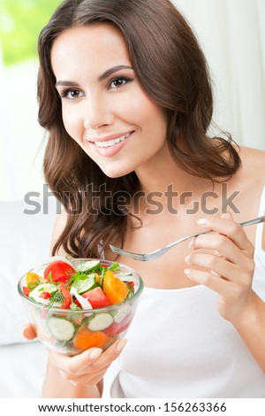 Portrait of happy smiling young woman with vegetarian vegetable salad, indoors - stock photo
