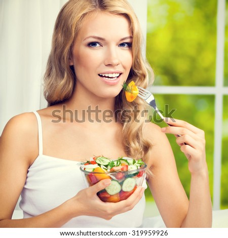 Portrait of happy smiling young woman with vegetarian vegetable salad, indoors, square composition